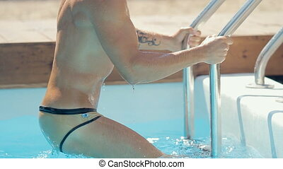 Sexy man in swimming trunks comes out the private pool outdoors by an aluminum ladder in slow motion