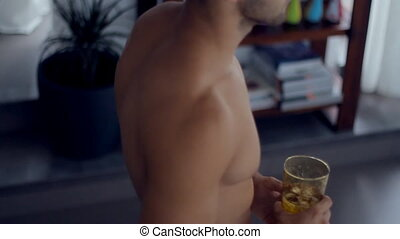 Sexy man in swimming trunks with a glass of ice water goes to the window and looks out into the street in slow motion