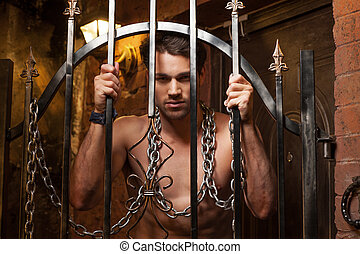 Sexy man standing behind metal gates. With metal chain on neck