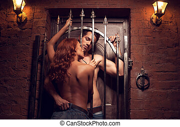 Sexy man with nude torso looking through the gate on topless girl. Staying back to the camera