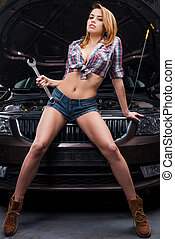 Sexy mechanic. Full length of beautiful young woman holding...