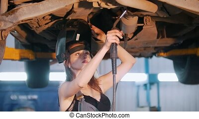 Sexy mechanic girl in a helmet fixing the car with a welding
