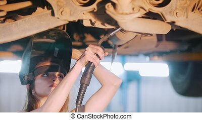 Sexy mechanic girl in a helmet repairs the car with a welding