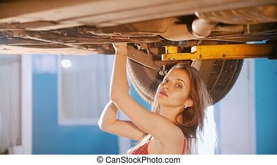 Sexy mechanic girl repairs the car with a spanner. Side angle