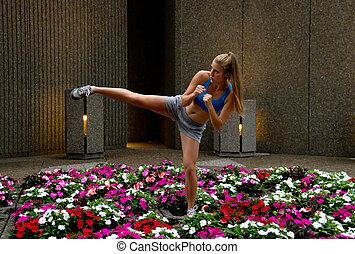 Sexy mixed-martial arts (MMA) woman kicking