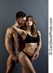 Sexy model and muscular hunk posing in studio