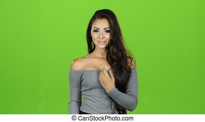 Sexy model brunette woman sends air kisses, green screen background