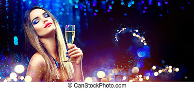 Sexy model girl drinking champagne over holiday glowing background