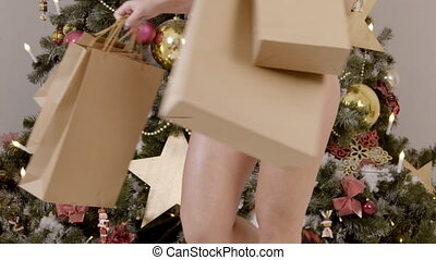 Sexy model is moving with gifts near New Year tree in room.