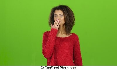 Sexy model mulatto woman sends air kisses, green screen background