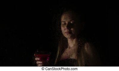 sexy model, posing behind transparent glass covered by water drops. young melancholy and sad woman drinks from a cocktail glass