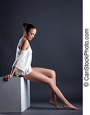Sexy model posing with bared shoulder and legs