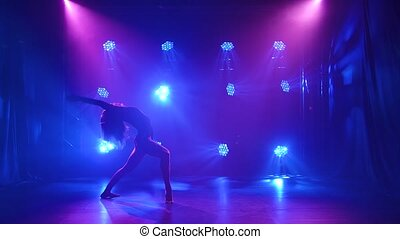 Sexy modern contemporary dance contempt performed by a flexible young woman. The dancer is enjoying the dance and hovering in a dark studio with neon lights. Silhouette. Slow motion