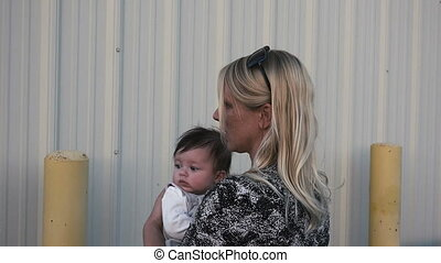 Sexy Mom Standing Holding Baby Turn - A sexy lady with a...