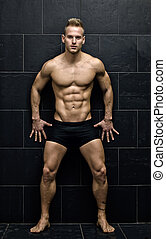 Sexy, muscular young man standing in underwear against dark wall, full body figure, looking at camera