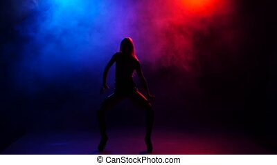 Sexy nightclub dancer performing on stage in bright lights, smoke