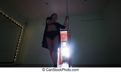 Sexy pole dancer girl dancing with a pole in a studio