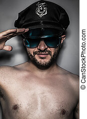 Sexy police, naked man with cap and glasses, saluting