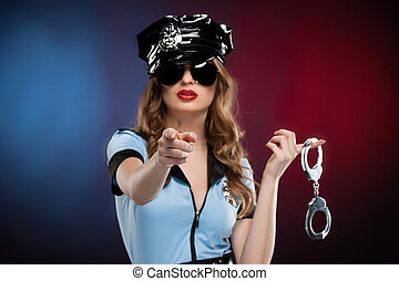 Sexy policewoman. Beautiful young policewoman in uniform holding a handcuffs and pointing you while standing isolated on colored background