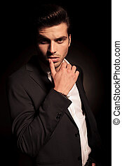 sexy provocative pose of a young fashion man in elegant suit and shirt on black background