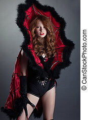 Sexy red-haired girl posing in devil costume
