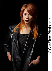 Sexy red-haired model posing in leather jacket
