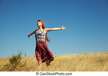 redhead woman in a dress outdoors