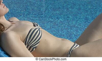 Sexy relaxed woman lying by the pool, gently touching her body