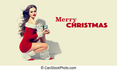 Sexy santa. Christmas beauty girl wearing red dress holding gifts. Brunette young woman portrait