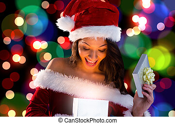 Sexy santa girl opening gift against light glowing dots...
