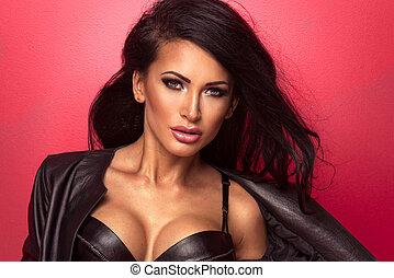 sexy, schöne , brünett, frau, in, schwarzes leder, damenunterwäsche, posierend, aus, rotes , hintergrund.