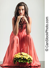sexy seated woman in red dress is thinking near flowers