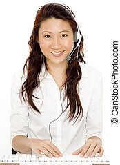 A beautiful asian woman with headset typing at a keyboard
