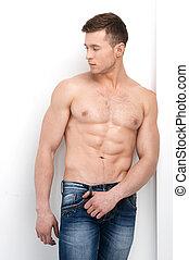 sexy, shirtless, macho, posar, en, cámara, y, mirar, away., posición, en, vaqueros, aislado, encima, fondo blanco