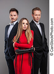 Sexy shoot of one beautiful girl in red dress and handsome men in black business suites. Standing together isolated over grey background