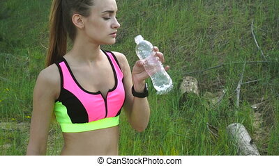 Sexy slim athletic woman drinks water after practicing