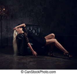 Sexy slim blond model lying and posing in fashion armchair in black dress on dark dramatic background with lamp