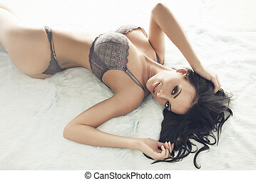 Sexy slim brunette woman posing in bed, looking at camera. Lady