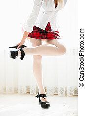 slim woman in school uniform taking of high heels
