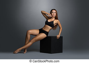 Sexy slim woman posing in black lingerie on cube