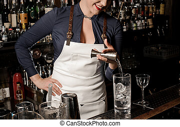 Sexy smiling female barman pouring vodka into a cocktail...