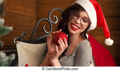 sexy smiling girl in santa claus hat holding christmas ball