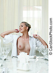 Sexy smiling girl stretches while sitting at table