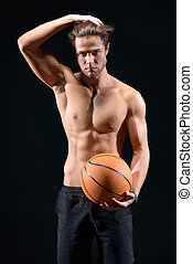 Sexy sportsman posing with ball