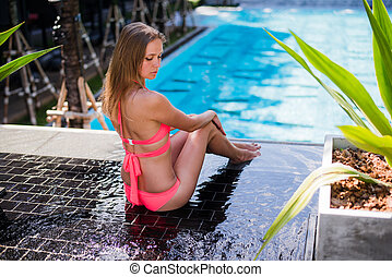 Sexy sporty tanned back of young blonde woman in bikini posing on luxury pool on tropic island vacation