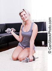 Sexy sporty woman is using dumbbell