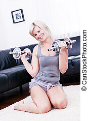 Sexy sporty woman is using dumbbells at home.