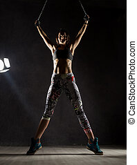sexy strong muscular woman with iron chain on dark background in the beam of a searchlight