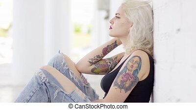 Sexy sultry young woman with a vampire tattoo on her arm...