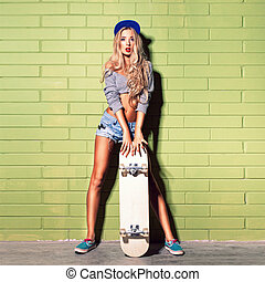 sexy suntan girl in short jeans shorts against green brick wall